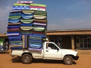Bil med mange madrasser på lasteplanet